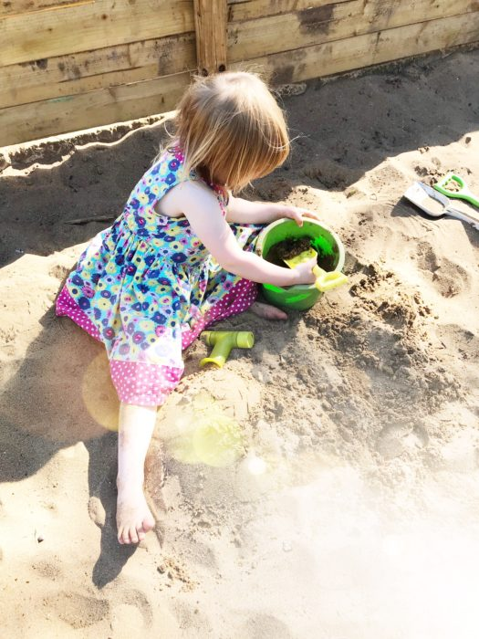 girl playing in sand pit