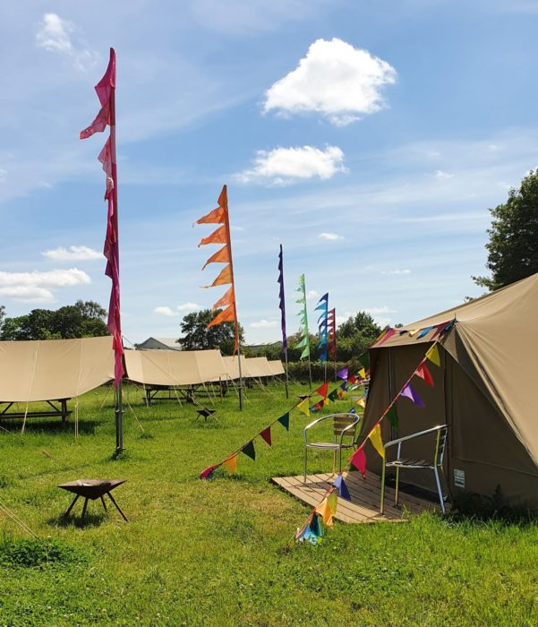 Canvas glamping tents and bright festival flags