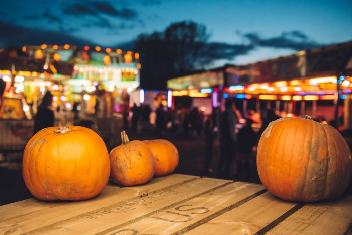 pumpkins lit by festoon lighting in the foreground, blurred fairground rides in the background.