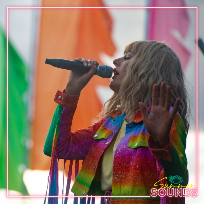 Taylor Swift Tribute in a rainbow coloured jacked with rainbow fringing sings in front of colour festival flags